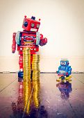 two vintage robots  with gold money on a wooden floor with reflection ,concept inequality,. poster