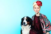 Fashion shot of a beautiful young woman with a dog. poster