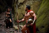 Muscular Spartan warrior with stunning ripped strong body walking away from his wife looking at her with love goodbye relationships love people medieval couples romance affectionate. poster