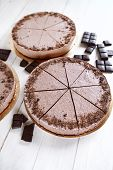 Chocolate mousse cheesecakes with a sprinkle of grated chocolate, with pieces of chocolate on a wooden table poster