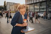 Busy woman is in a hurry, she does not have time, she is going to to drink coffeeon the go. Worker drinking and talking on the phone at the same time. Businesswoman doing multiple tasks. Multitasking business person. poster
