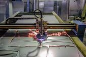 Plasma cut machine with program control cutting steel sheet with sparks in metalwork factory. poster