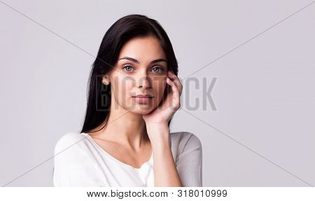 Beautiful Brunette Woman With Hand Near Face Wearing White Pullover On Light Grey Studio Background