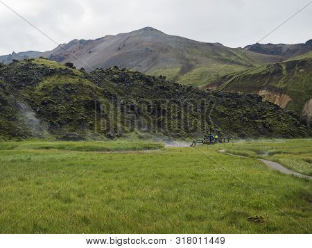 Group of tourist people relaxing in a natural hot spring in thermal baths in Landmannalaugar camp site, Iceland. Grass meadow, lava fields and mountains in background poster