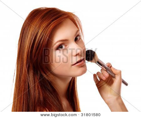 Portrait of beautiful young redheaded woman with esthetician making makeup. Isolated on white background