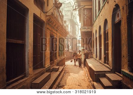 Varanasi, India: Local People Walking On Narrow Streets With Tall Houses In Historical Indian City O