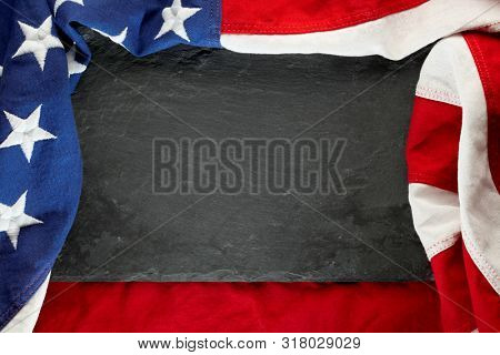 US American flag on black slate stone background. For USA Memorial day, Veteran's day, Labor day, or 4th of July celebration. With blank space for text.