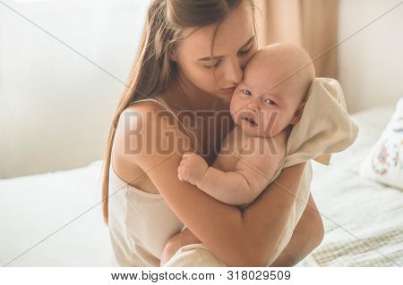Home Portrait Of A Newborn Baby With Mother On The Bed. Mom Holding And Kissing Her Child. Concept B