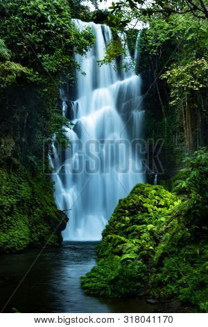 Waterfall Landscape. Focus On Waterfall, Blurred Leaves. Beautiful Waterfall In Tropical Rainforest.