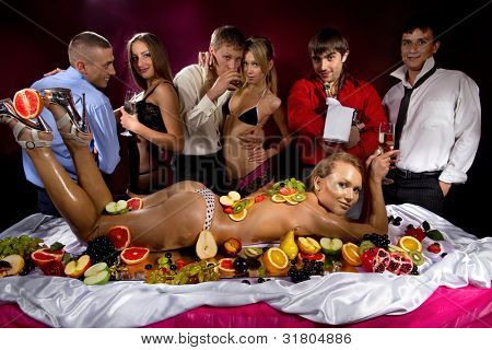Guys having fun with women decorated  by fruits