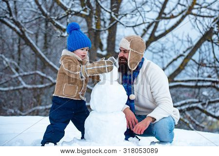 Father And Son Making Snowman In The Snow. Handmade Funny Snowman. Christmas Holidays And Winter New