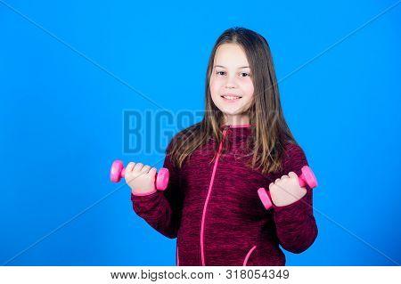 Child hold little dumbbell blue background. Sport for teens. Easy exercises with dumbbell. Toward stronger body. Rehabilitation concept. Girl exercising with dumbbell. Beginner dumbbell exercises poster