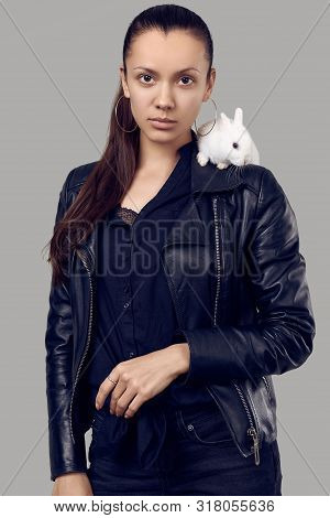 Portrait Of Gorgeous Latin Women In Fashion Leather Jaket With Cute Little Rabbit On Gray Studio Bac