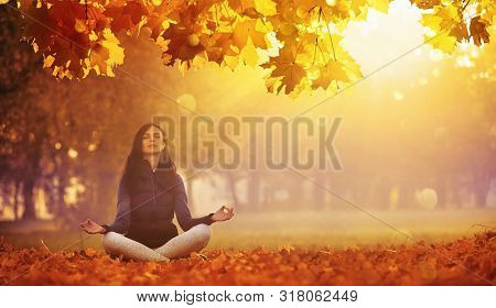 Beautiful Young Woman Meditating Outdoors In Autumn Park. Fall Scene