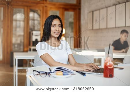 Smiling Beautiful Young Girl Student Studying In Cafe, Smiling Camera As Typing Essay Using Laptop,