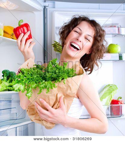 Diät Konzept .diet. schöne junge Frau in der Nähe der Kühlschrank mit gesunden Lebensmitteln. Obst und Gemüse