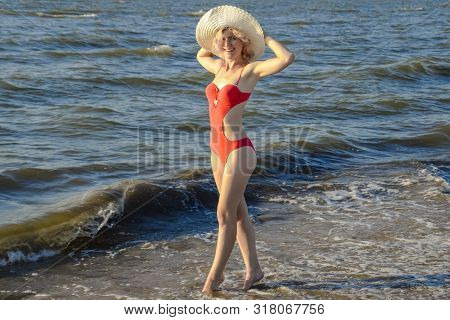 A Girl In A White Hat And In A Red Bathing Suit Stands On The Seashore.