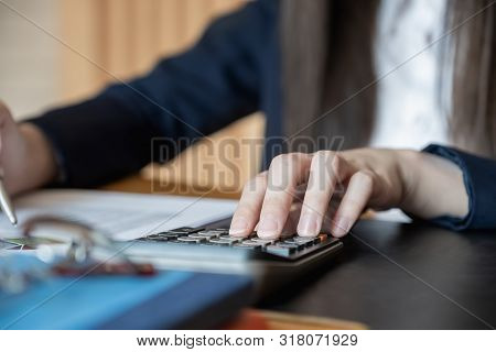 Businessmen, Accountants, Are Working At The Office To Verify The Accuracy Of The Account Using A Ca