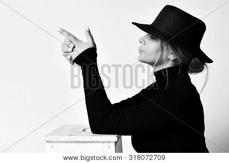 Black And White Portrait In Profile Of Blonde Woman In Black Hat With Brim And Turtleneck Sweater Do