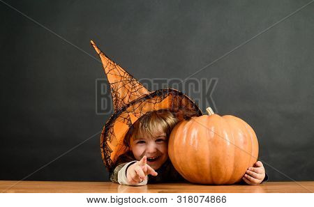 Little Boy In Witch Hat With Halloween Pumpkin Pointing To You. Trick Or Treat. Preparation Hallowee