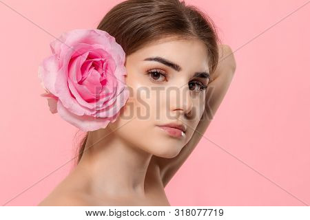 Close-up Portrait Of A Beautiful Young Girl Looking At The Camera Holding Pink Rose Flower Close To