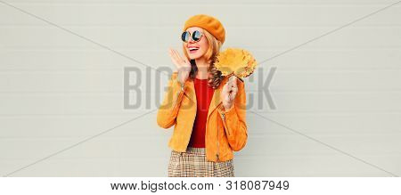 Autumn Season! Happy Surprised Woman With Yellow Maple Leaves In French Beret Posing Over Gray Wall