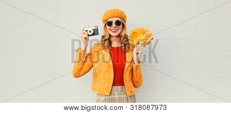 Happy Smiling Woman Holding Autumn Yellow Maple Leaves, Retro Camera Taking Picture In French Beret