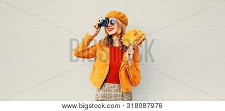 Woman With Autumn Yellow Maple Leaves, Retro Camera Taking Picture In French Beret Over Gray Wall Ba