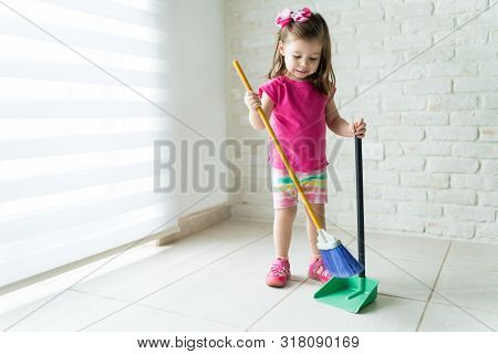 Little Female Kid Cleaning Living Room With Broom At Home
