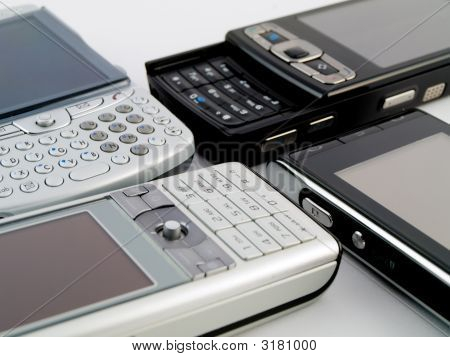 Stack Pile Of Several Modern Mobile Phones Pda Cell Handheld Units On White Background