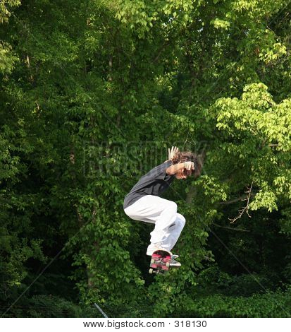 Skateboarder Jumping Near Trees