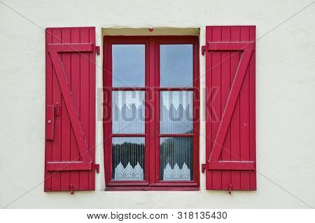 Sunny View Of A Windows Of An Old Farm House With Red Shutters, Where A Curtain Of Handmade Crochet