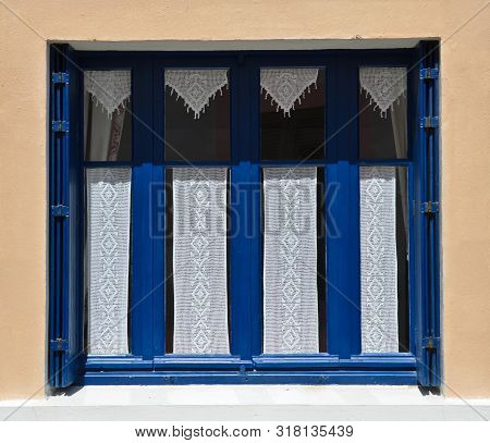 Sunny View Of A Windows Of An Old Farm House With Blue Shutters, Where A Curtain Of Handmade Crochet