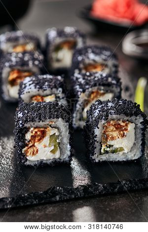 Macro shot of unagi maki rolls with rice, cream cheese, eel, cucumber, flying fish black caviar and nori closeup. Fresh japanese uramaki rolls with tobiko on black slate plate background
