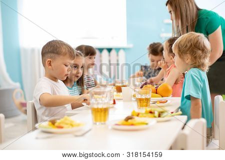 Kids Have A Dinner In Kindergarten. Little Boys And Girls From The Group Of Children Sitting At Tabl