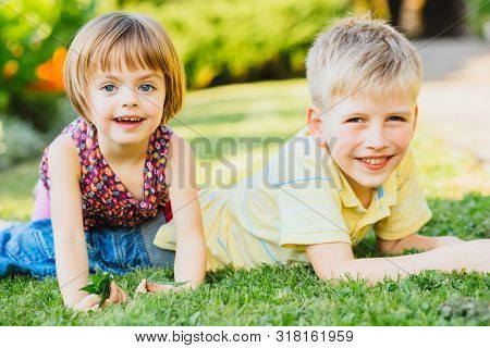 Two Children, Big Brother And His Little Sister Are Laying On Green Grass And Smile, Laughing, Wallo