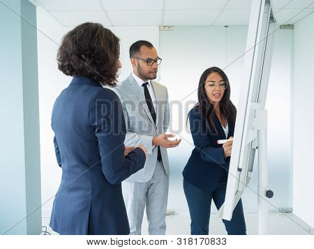 Manager Presenting Company Strategy To Customers. Business Woman Drawing On Board, Her Two Colleague