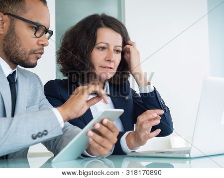 Business Analysts Checking Data On Tablet And Laptop. Business Man And Woman Sitting At Office Table
