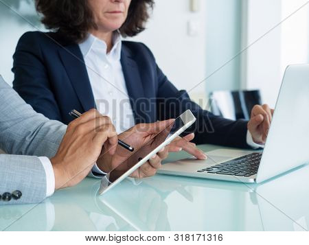 Business Professionals Checking Reports On Tablet And Laptop. Business Man And Woman Sitting At Offi