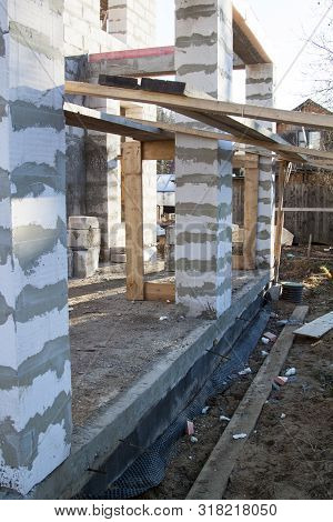 interior of a country house under construction. Site on which the walls are built of gas concrete blocks with wooden formwork poster