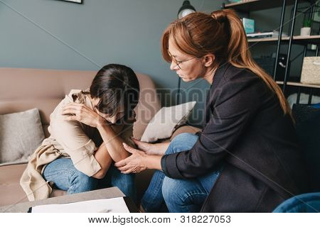 Photo of depressed caucasian woman having conversation with psychologist on therapy session in room