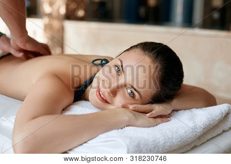 Beautiful Young Woman Receiving Massage In Spa Salon. Body Care. Spa Body Massage Woman Hands Treatm