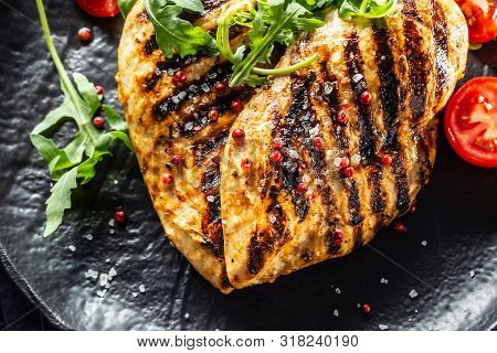Chicken Breast Grilled With Spices Peper Salt Tomatoes And Arugula
