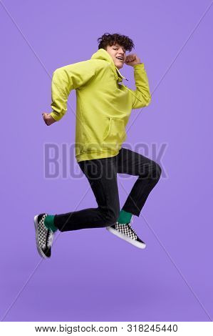 Full Body Side View Of Youngster In Stylish Outfit Smiling And Posturing While Jumping High Against