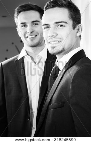 Portrait Of Attractive Couple Of Men Wearing Suits Smiling At Camera