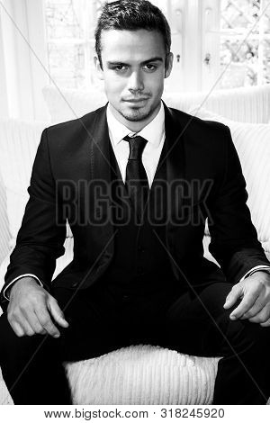 Handsome Man In Suit Sitting In Armchair Looking At Camera With Patio Doors In Background