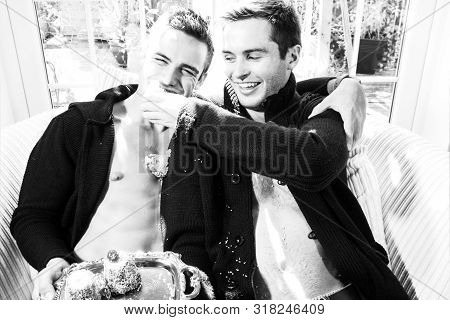 Male Gay Couple Sat On Armchair Laughing And Smiling While Feeding Each Other Cake.