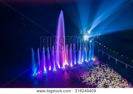 Waterworks At The Night On The Water Surface, Decorated And Played Color By Lighting Spot Light.