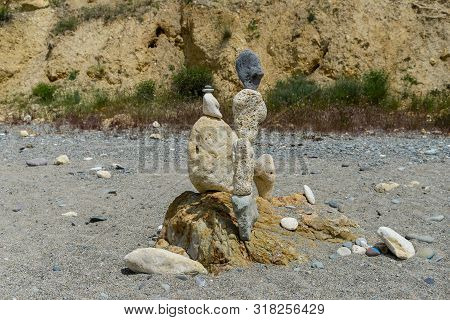 A Stone Sculpture Stands On A Deserted Beach
