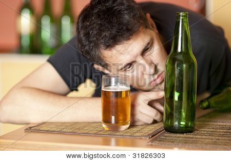 Drunkard.  Man drinking a beer. Focus on bottle